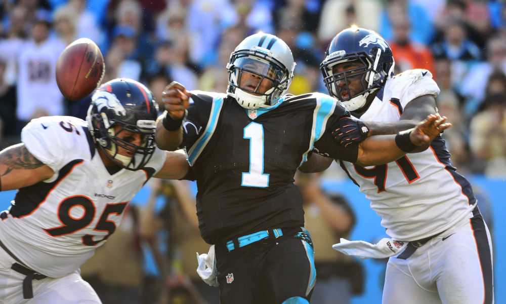 Nov 11, 2012; Charlotte, NC, USA; Carolina Panthers quarterback Cam Newton (1) is hit as he throws a pass by Denver Broncos defensive end Derek Wolfe (95) and defensive end Robert Ayers (91) in the third quarter at Bank of America Stadium. Mandatory Credit: Bob Donnan-USA TODAY Sports