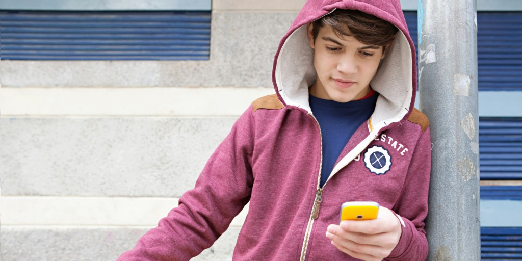 Teenager using smartphone in basketball court.